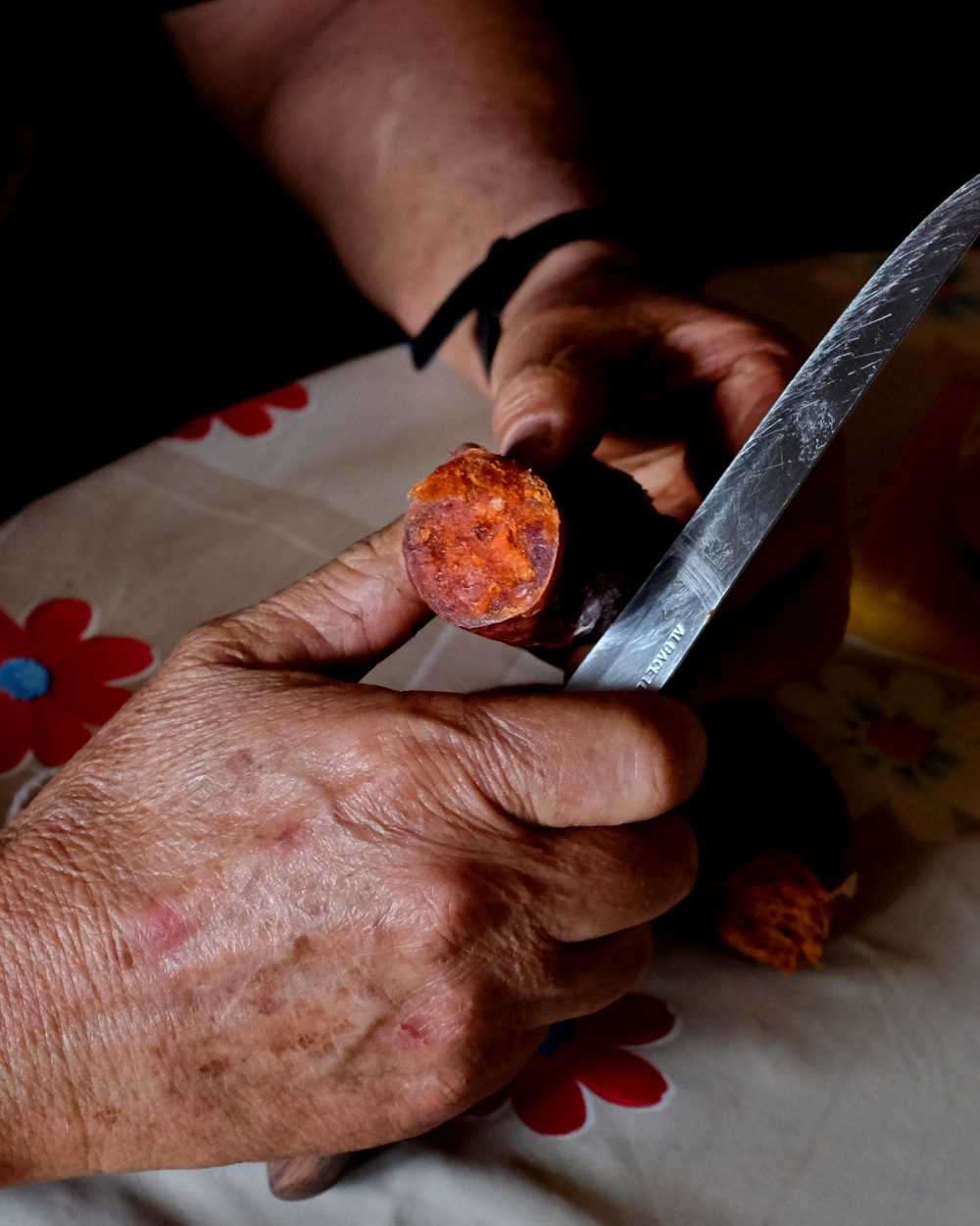Farmer Paco Garcia Barra slices up sausage spiced with pimentón made from his peppers.​